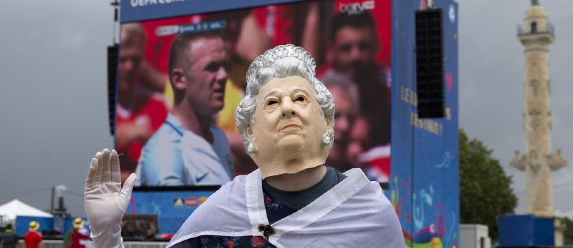 A British fan wearing a mask representing Britain's Queen Elizabeth II waves to other fans as they watch the Euro 2016 Group B soccer match between England and Wales in Bordeaux's fan zone, France, Thursday, June 16, 2016. (AP Photo/Hassan Ammar) - © AP