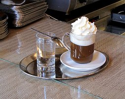 The Mozart Kaffee is served on a stainless steel platter with a short glass of water.